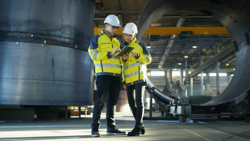 Male and Female Industrial Engineers in Hard Hats Discuss New Project while Using Tablet Computer. They Make Showing Gestures.They Work at the Heavy Industry Manufacturing Factory. Long Shot.