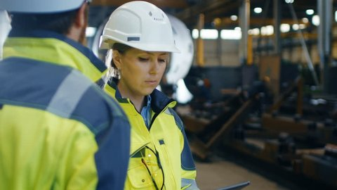 Male and Female Industrial Engineers in Hard Hats and Safety Jackets Discuss New Project while Using Tablet Computer. They Work at the Heavy Industry Manufacturing Factory. 4K UHD.