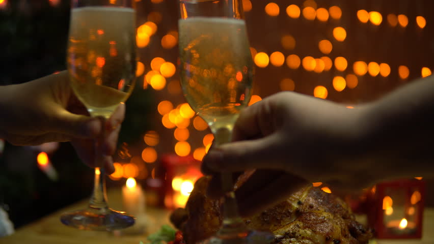 Two people raise glasses of sparkling champagne,toasting and clinking at a celebration at the dinner table with a toasted bird against the background of yellow electric lights.   Shutterstock HD Video #32794111
