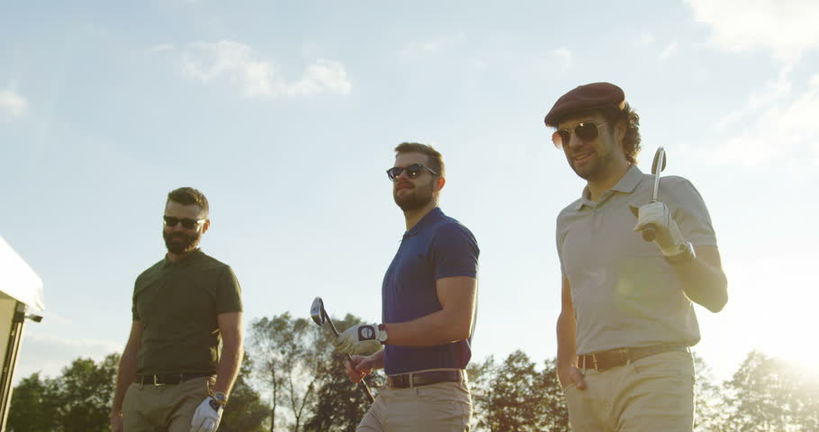 Three Caucasian attractive men with clubs going to start playing golf on the nice sunny day. Outdoors | Shutterstock HD Video #32805118