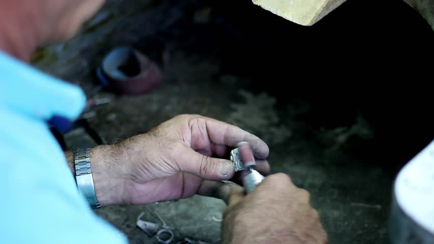 The man is sharpening silver, Manufacture of carved articles from silver by hands, handwork on silver in Armenia, decoration of manual production of silverware. Armenian silver production. UHD.
