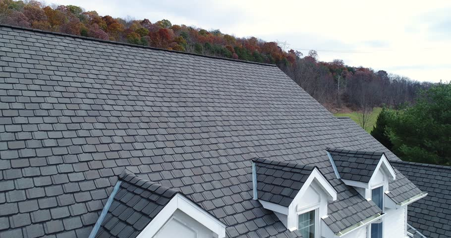A slow reverse aerial view revealing a farmhouse's roof and shingles.