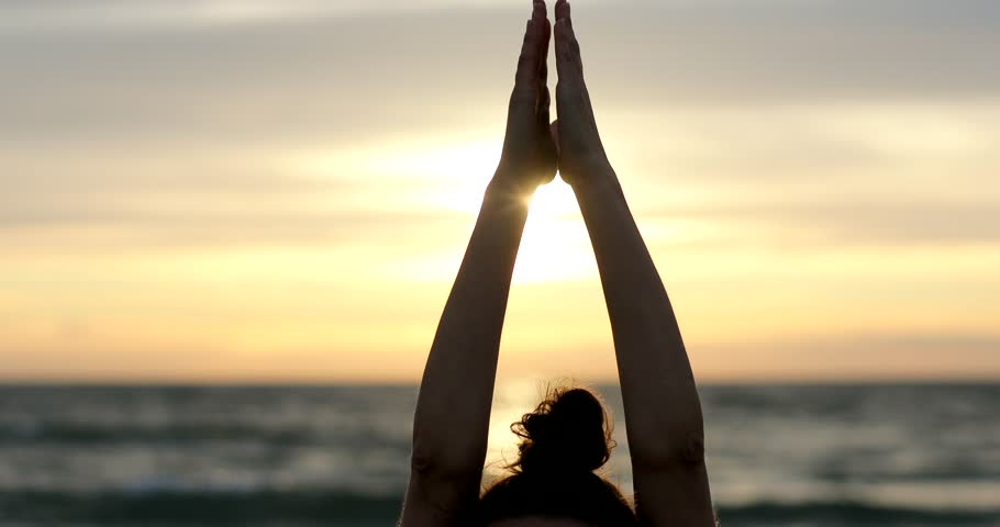 Raising hands in Namaste gesture above head on sun sunset or sunrise sea sky background centered close up 4k. Yoga woman holds arms up palms together stretching practicing Surya Namaskar or tree pose