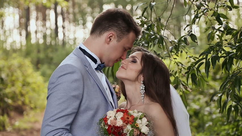 The Bride And Groom In Forest They Are Close Look Into Each Other S