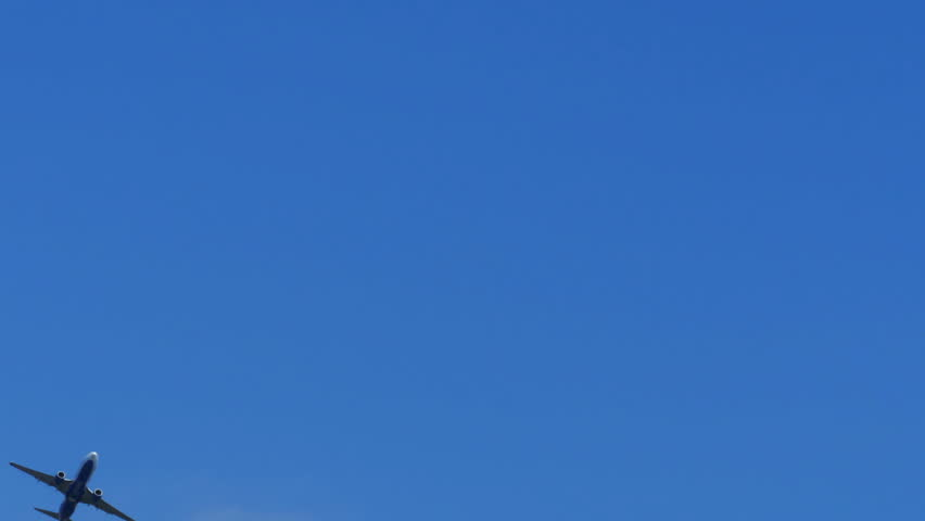 The passenger airplane is flying far in the blue sky. Beautiful background of a flying airplane. Airplane flying deep blue sky. Commercial jet flying away far into the sky.