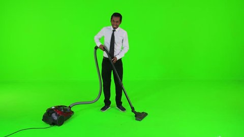 Young businessman vacumming the floor rapidly over a green screen. upset, long shot.