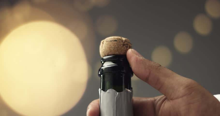 Close up video of man's hands opening a bottle of champagne on gray background with lights and flares