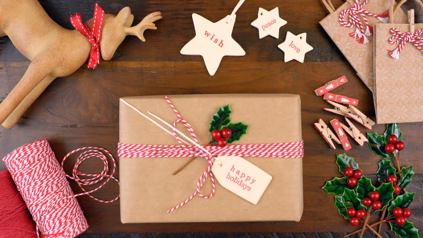 Christmas gift wrapping overhead in rustic theme with brown Kraft paper, string and natural ornaments