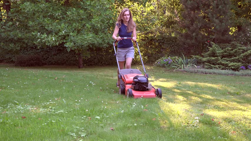 Female woman moves with lawnmower and mows green grass. Stone cobbled path in garden. Evening sunlight shadows on meadow. Static shot. 4K | Shutterstock HD Video #32924938