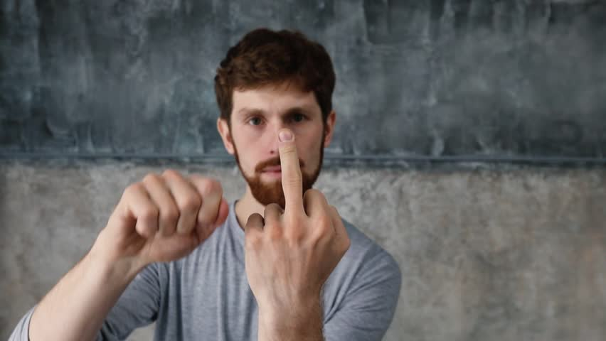 Portrait of a young Red-haired bearded man showing middle finger gesturing fuck. White man makes fuck gesture with a hand on light gray background. Guy slowly showing middle finger sign fuck off