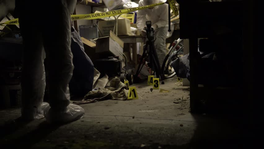 Forensics crime scene searching for clues in murder investigation at night. Photographer and torch, Collecting evidence. Part of a crime scene at night collection. Police investigation in 4K.