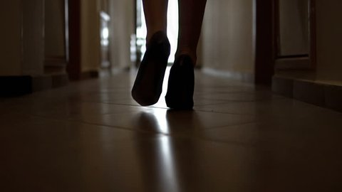 Silhouette of a fashion model female walking along a dark corridor in high hills shoes, SLOW MOTION