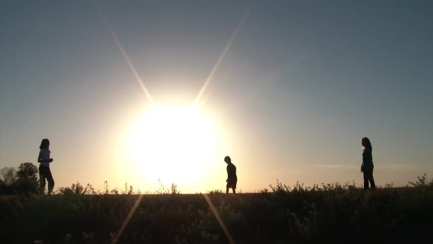 Three kids are throwing a pink ball on top of a small hill backlit by sunlight back and forth with success. | Shutterstock HD Video #3293828