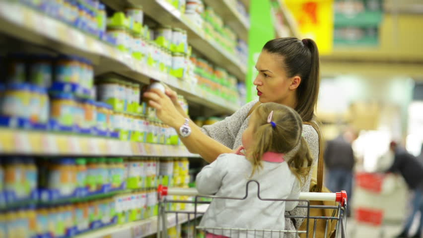 Side View of Happy Family Choosing Products in the Shop. Smiling Woman is Standing Near Shelf With Goods, Little Girl is Sitting in Shopping Cart. | Shutterstock HD Video #32949046