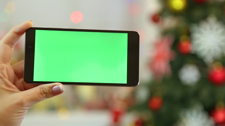 Closeup of female hands holding black modern smartphone in hands at glowing Christmas home interior. Adult woman uses digital device with blank green screen. Real time full hd video. | Shutterstock HD Video #32984587