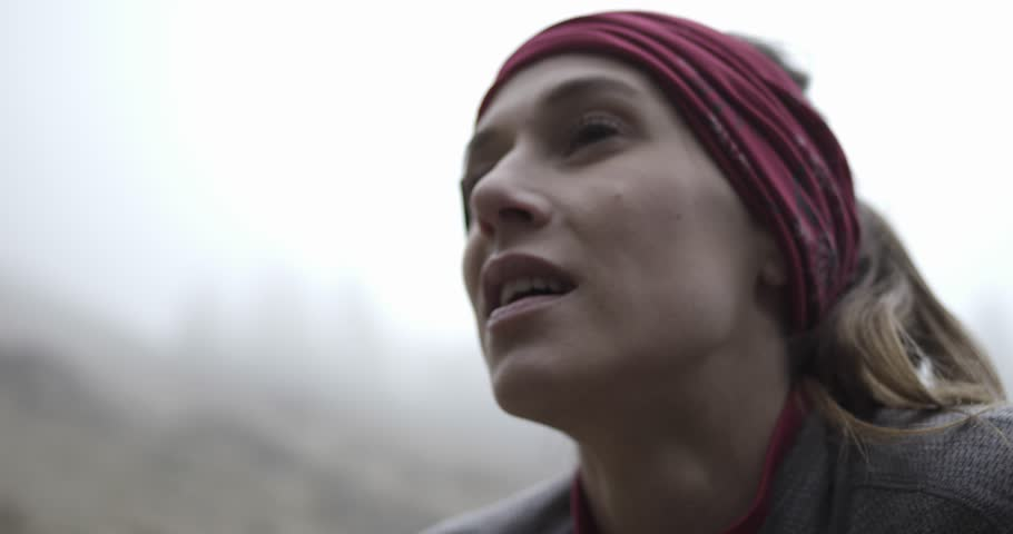 Athlete girl resting after run. Detail on face breathing.Real people woman runner sport training in autumn or winter in wild mountain outdoors nature, bad foggy weather.4k 60p slow motion video