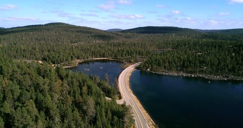 Arctic road, Cinema 4k aerial view over a asphalt road between, pine tree forest, a lake and tunturi fjeld mountains, on a sunny autumn day, near Inari, in Lapland, Finland