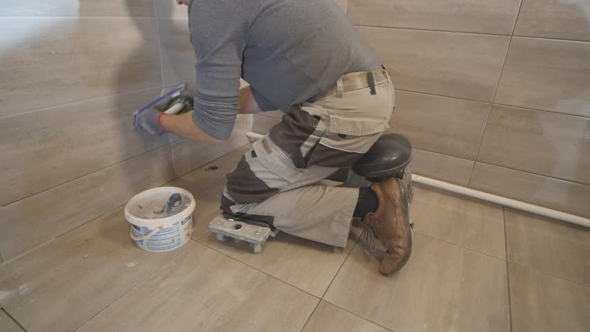 Worker putting fugue on the wall in the kitchen. Tile grouting