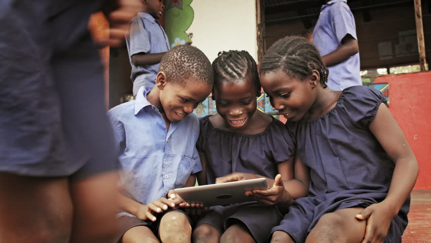 4k of African school students / pupils using tablet computer during lunch break at school.