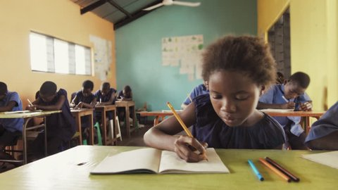 4k close view of pupils in classroom of African children writing English in school notebooks.