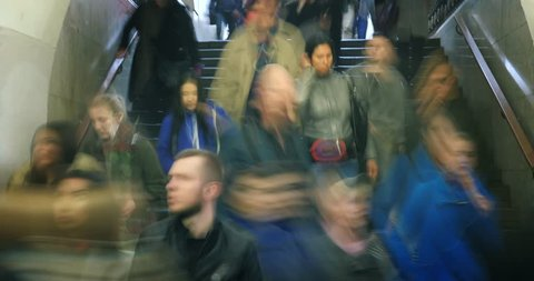Crowds of people exiting stairway in subway station, blurred in motion. Busy city life. 4K UHD timelapse.