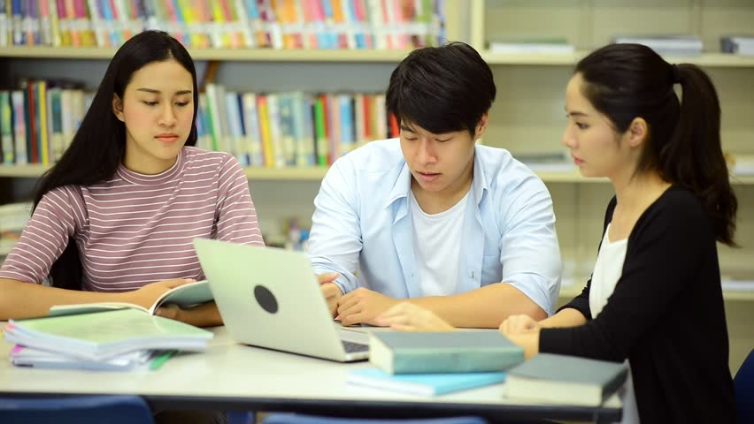 Young students study hard in library. Happy Asian female and male university students doing study research in library with books on desk, notebook. For back to school education diversity concept. | Shutterstock HD Video #33024484