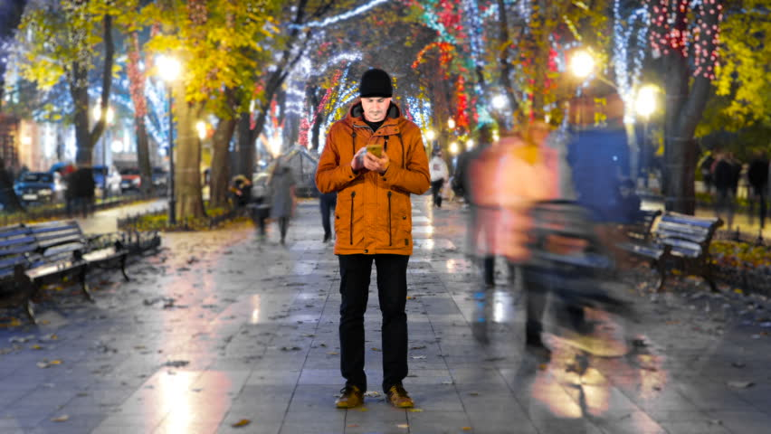 Timelapse of man standing still with smartphone on crowded walkway park boulevard with christmas garlands at night. People moving fast. Concept of flowing time and technologies