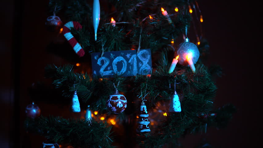 Plate numbered 2018 on a Christmas tree among toys and yellow electric lights, New Year's background. | Shutterstock HD Video #33030622