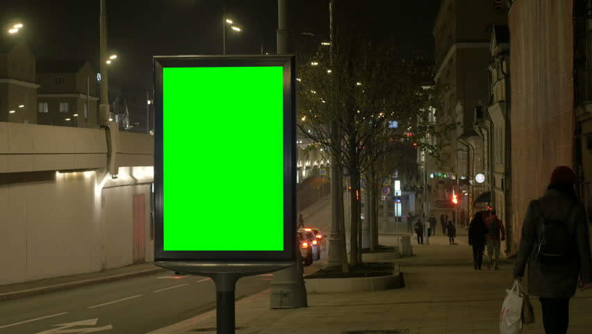 People walk on street pavement passing close city light box with green screen against driving cars at night