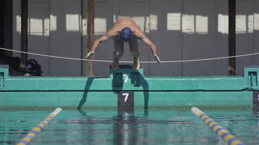 Slow Motion Shot Of A Professional Male Swimmer Jumping Off Swim Start Block