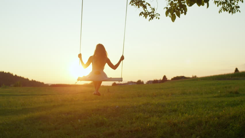 SLOW MOTION LENS FLARE: Smiling young woman swaying on rope swing under big tree at sunrise. Pretty girl in white dress swinging over the sun at golden sunset. Beautiful lady enjoying summer evening | Shutterstock HD Video #33082378