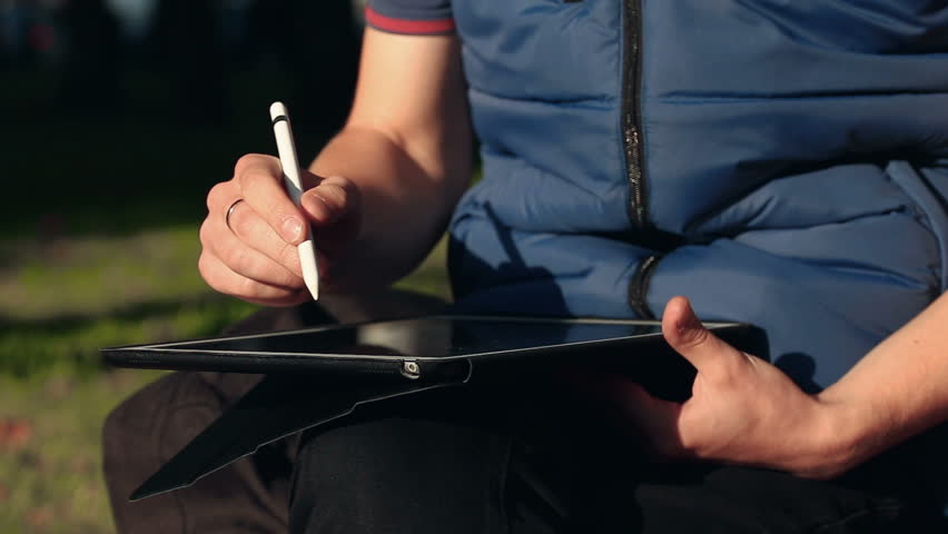 Closeup shot of painter's hand scaling and drawing a sketch on tablet using stylus at park. | Shutterstock HD Video #33082762