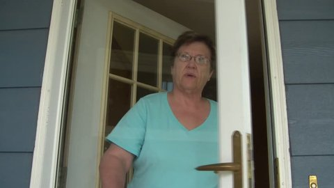 Older lady answers her door and then proceeds waving gesture to come into her home.