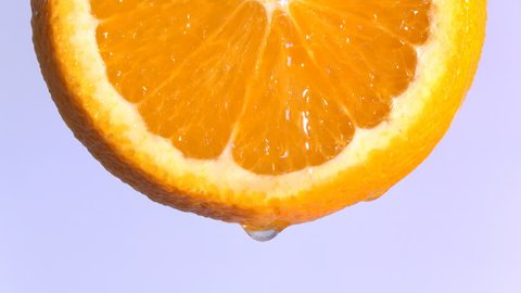 water or oils dropping on an orange slice , fruit for diet and healthy food