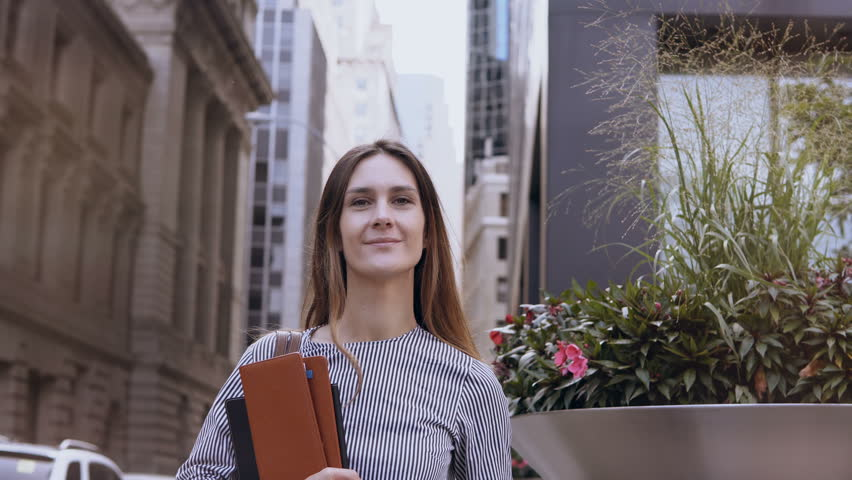 Portrait of young beautiful successful businesswoman near office building in New York, America. Female holds documents. | Shutterstock HD Video #33105202