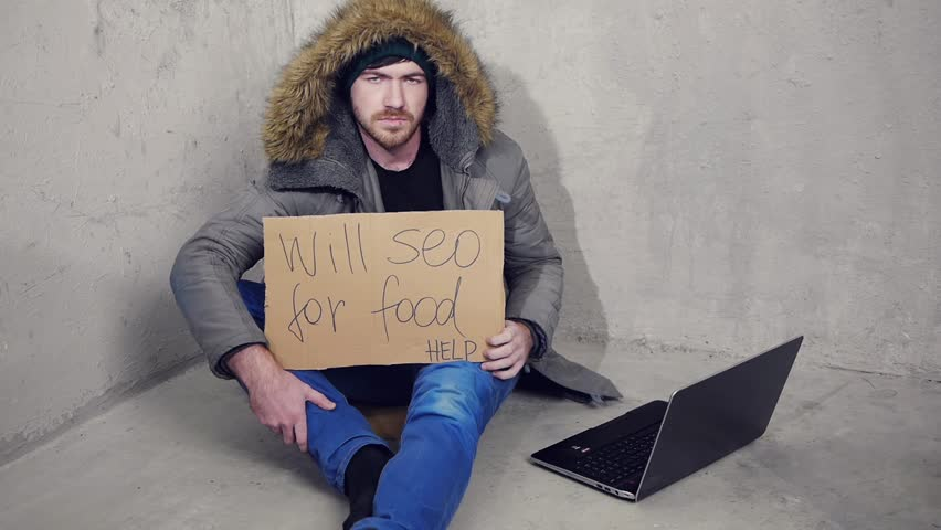 homeless man sitting on the floor with a cardboard asking for a help