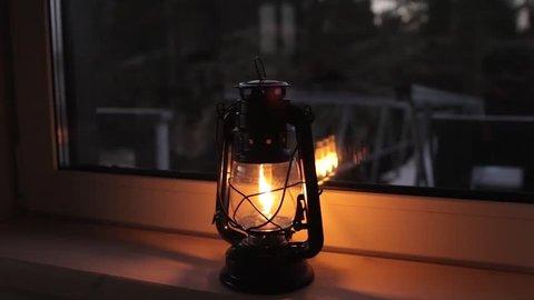 burning kerosene lantern on the window