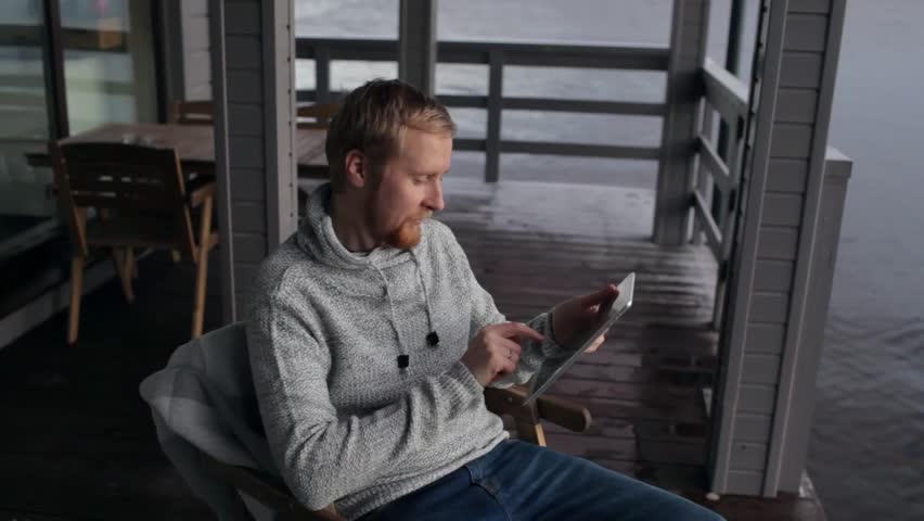 Man with a tablet sits on the terrace of a house on the lake | Shutterstock HD Video #33111571