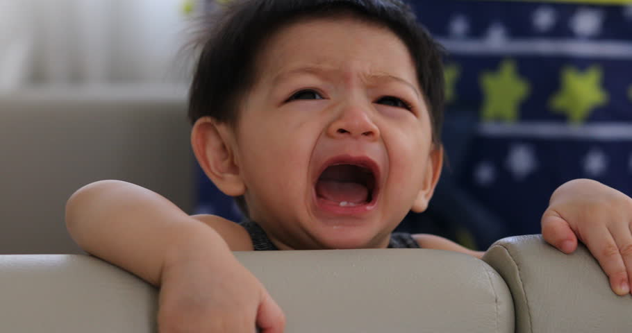 cute baby boy crying in soft mattress partition protection area
