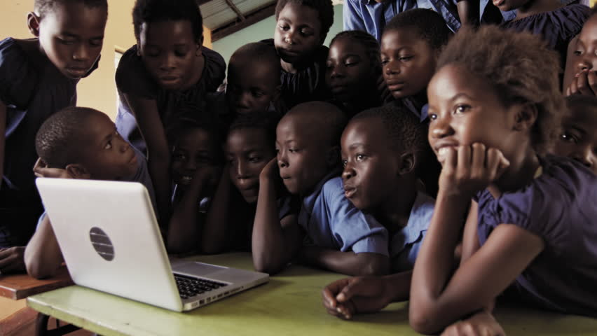 4k of group of pupils viewing a laptop computer in African classroom.