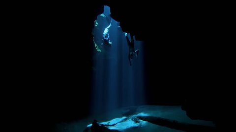 Underwater, Slow Motion, woman freediving in gorgeous crystal clear lake exploring beautiful cave