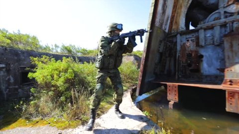 Soldier searching for enemy. Rusty military ruins. Russian soldier with AK