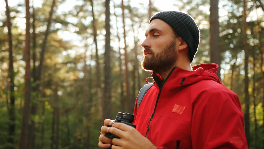Portrait of the young handsome man with a beard standing in the middle of the forest and looking in the binoculars. Sunny day. Close up. Outdoor