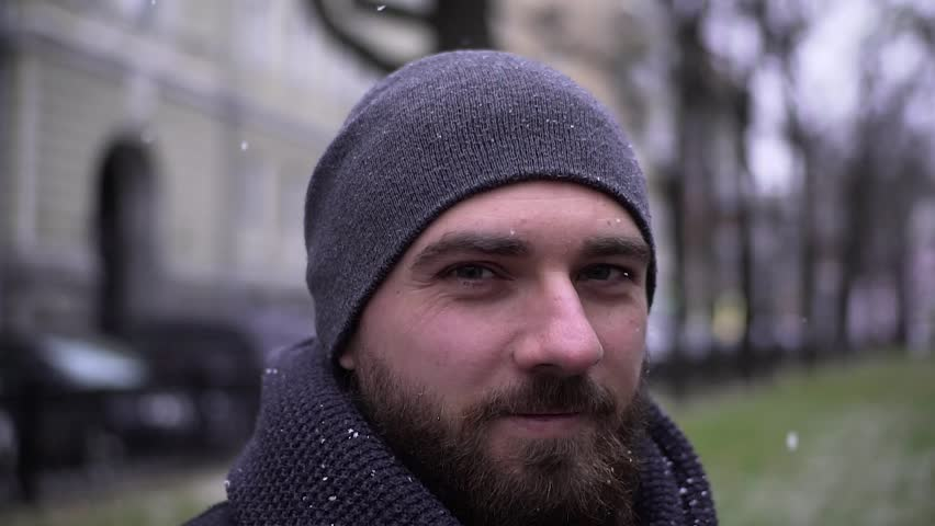 Portrait of a cheerful young man in a street in winter in the city