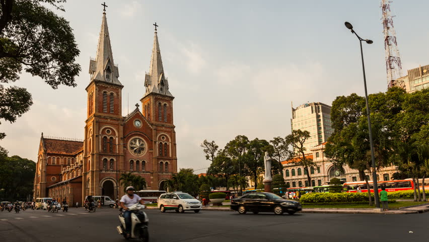 HO CHI MINH CITY, VIETNAM - JANUARY 27, 2013: Timelapse view on Notre-Dame Cathedral in Ho Chi Minh City. Traffic with unrecognizable people can be seen in the foreground.