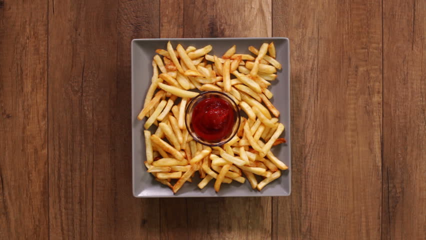 Hands taking french fries from a rotating plate - dipping it in ketchup, time lapse footage, fast food concept