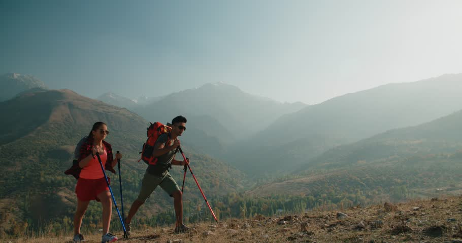 Young Asian couple Hiking in the mountains on Sunny day, steadycam shot | Shutterstock HD Video #33281758