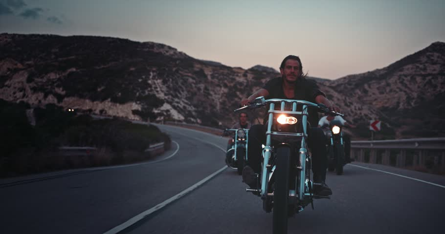 Young macho bikers riding motorbikes on mountain highway at sunset during road trip adventure