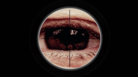 A sniper scope pointing at the big eye of a man, looking in camera, expressing pain. Detail macro shot.