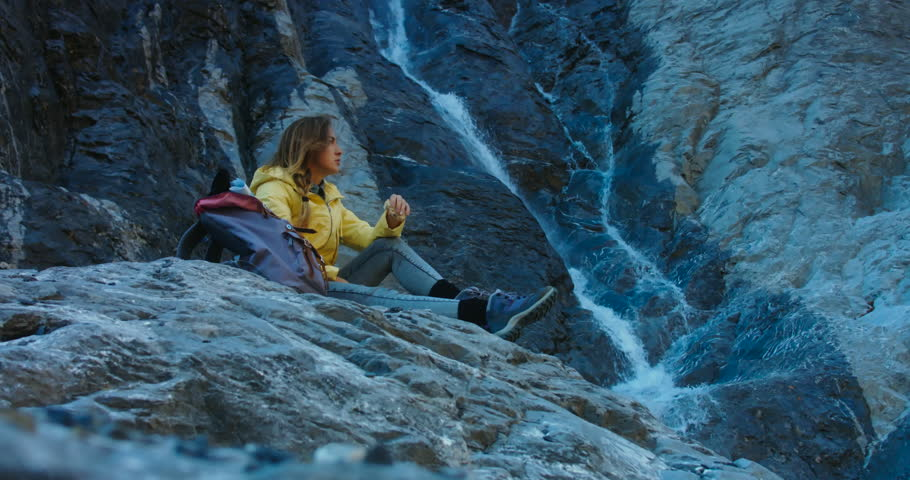 CINEMAGRAPH - SEAMLESS LOOP Attractive female tourist with a backpack having a lunch near mountain waterfall